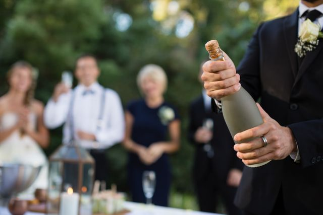 Groom opening champagne bottle at park