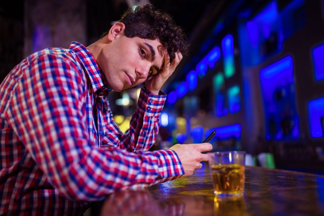 Portrait of sad young man sitting at bar counter