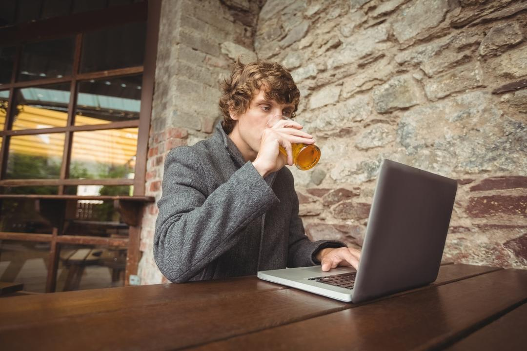Mid section of man holding glass of beer and using laptop