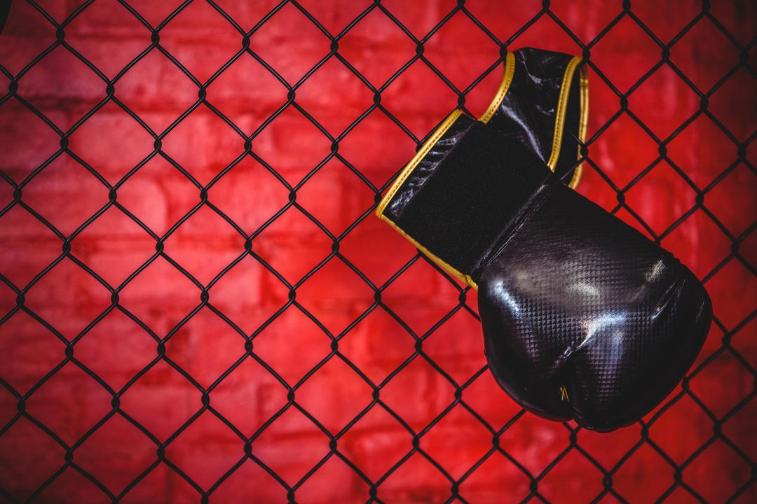 Boxing glove hanging on wire mesh fence in fitness studio