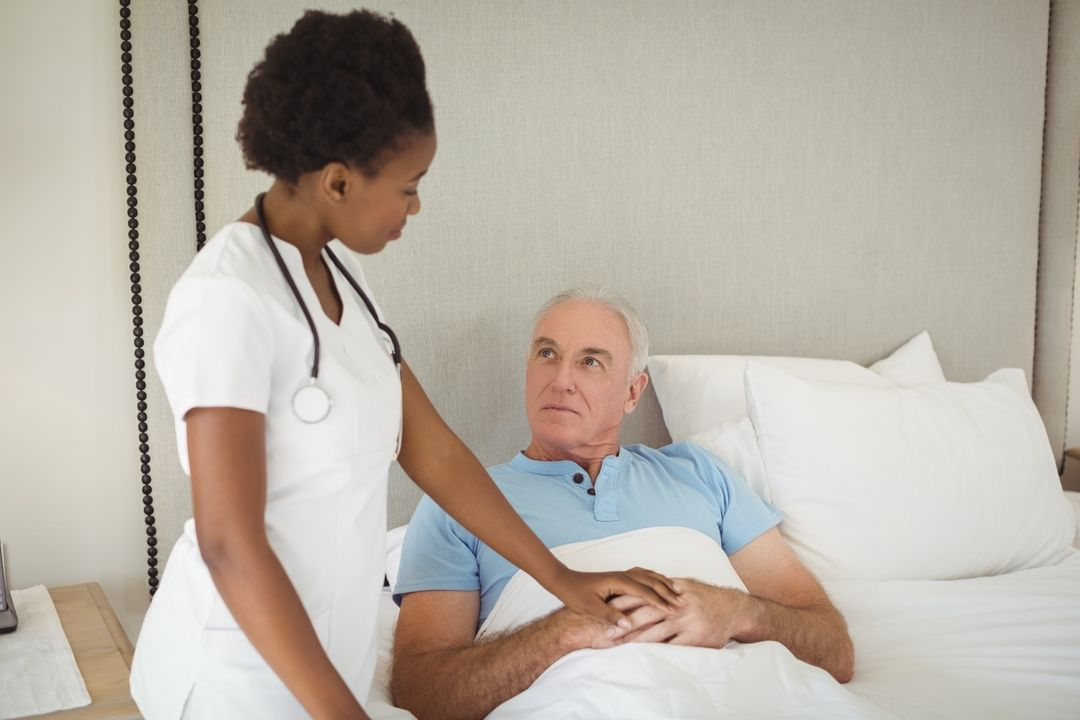 Nurse interacting with senior man on bed at bedroom Free Stock Images from PikWizard