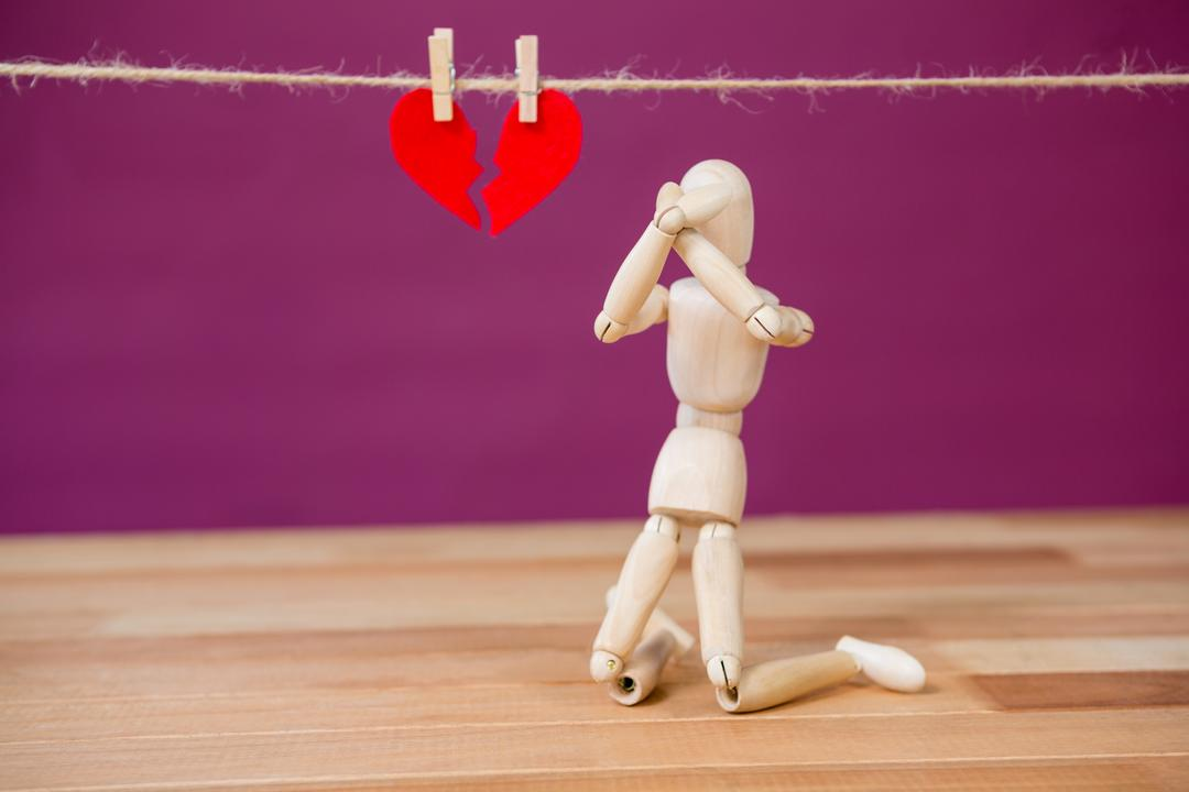 Conceptual image of figurine kneeling in front of broken heart Free Stock Images from PikWizard