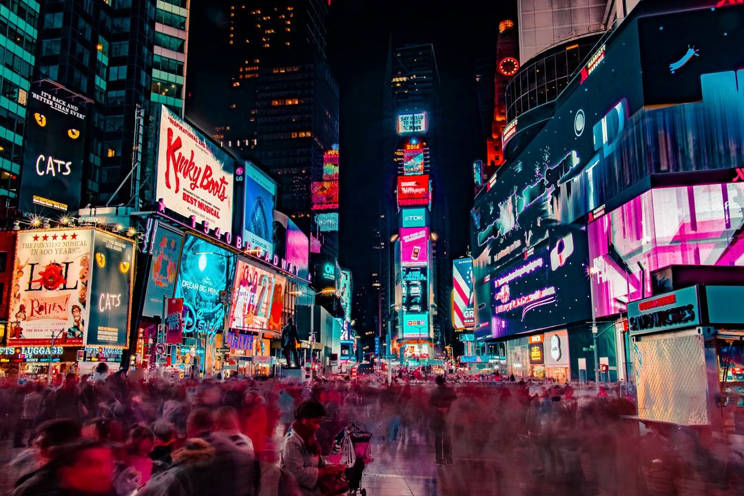 Slow motion image of people walking through New York City with bright billboards in the background