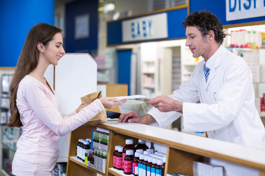 Pharmacist giving medicine package to customer at counter in pharmacy Free Stock Images from PikWizard