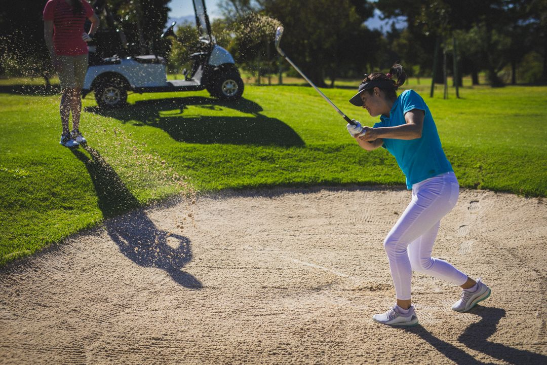 Caucasian woman hitting golf ball out of sand trap at golf course. Sports and active lifestyle concept. Free Stock Images from PikWizard