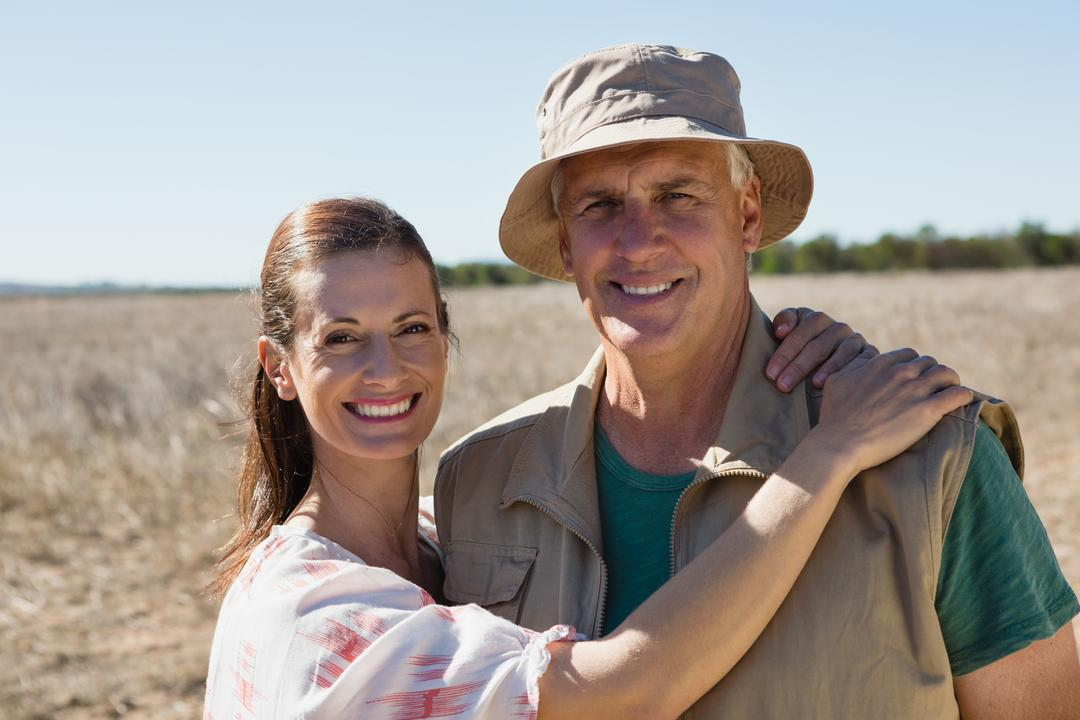 Portrait of couple standing on landscape during sunny day Free Stock Images from PikWizard