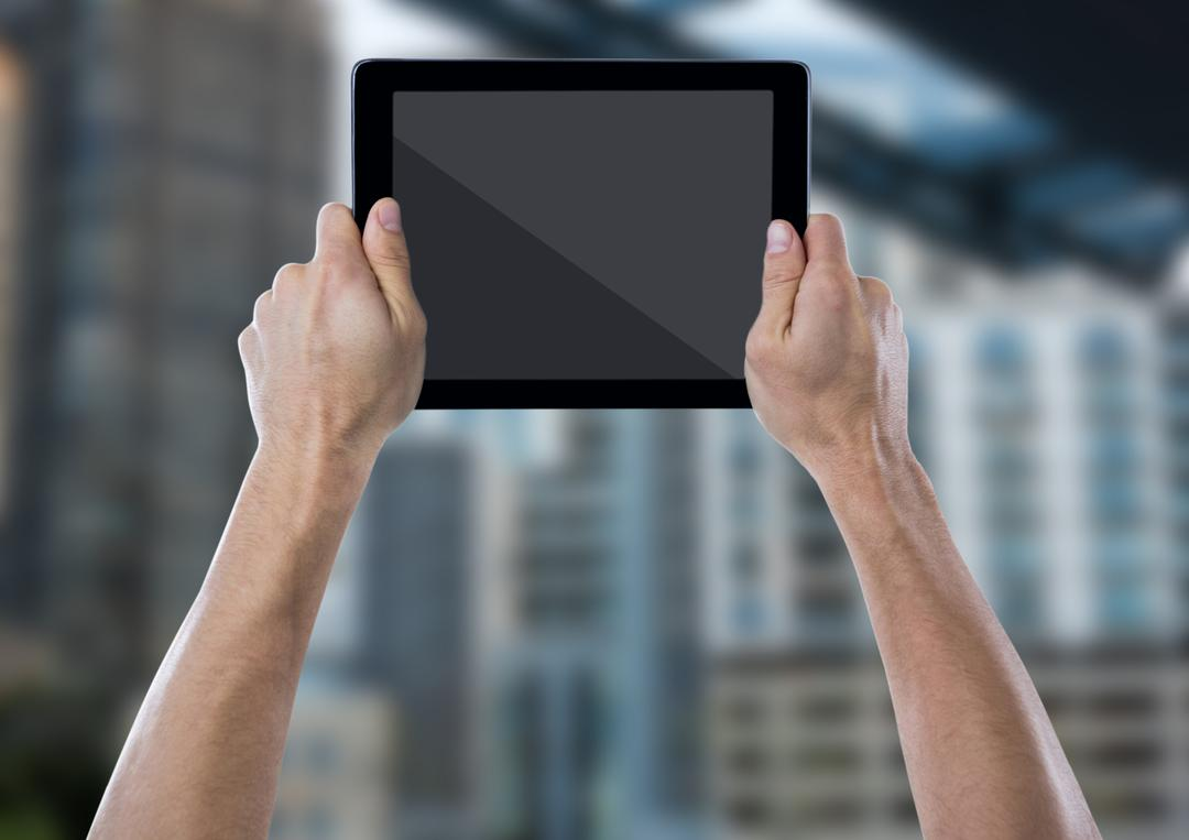 Digital composite of Hand with tablet against blurry building Free Stock Images from PikWizard