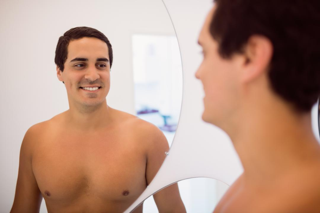 Man smiling while standing in front of the mirror in clinic