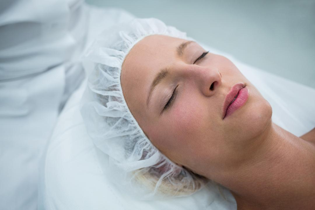 Patient lying on bed while receiving cosmetic treatment in clinic Free Stock Images from PikWizard