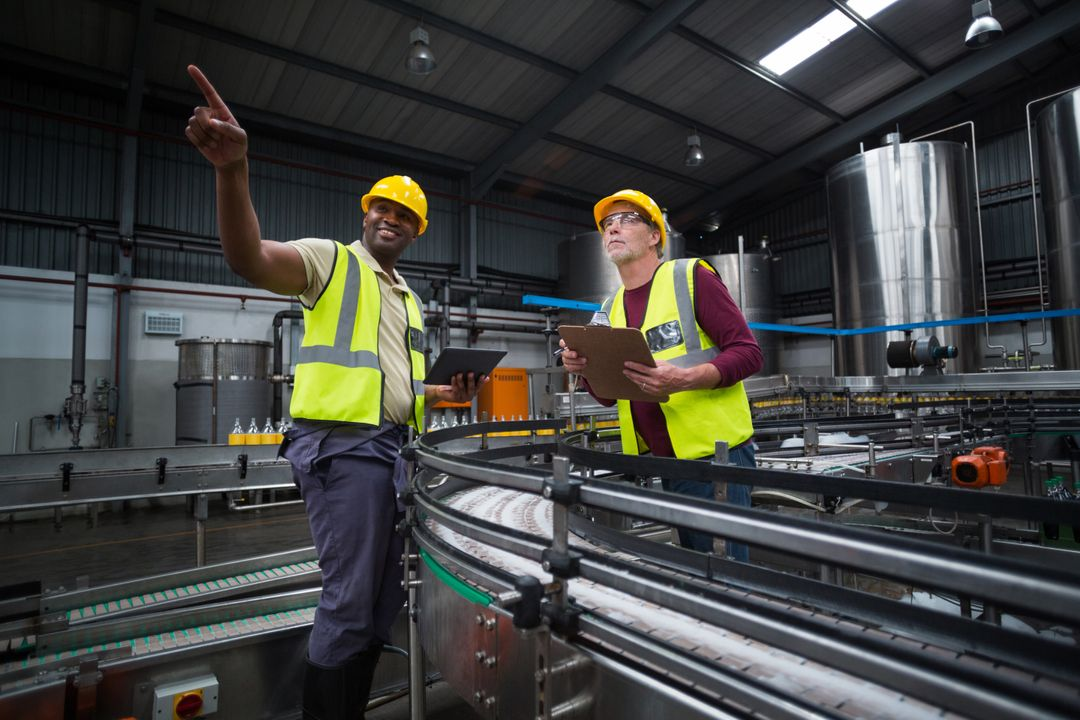 Two factory workers looking up in drinks production plant Free Stock Images from PikWizard