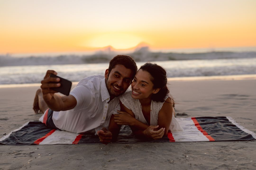 Happy couple taking selfie with mobile phone on the beach