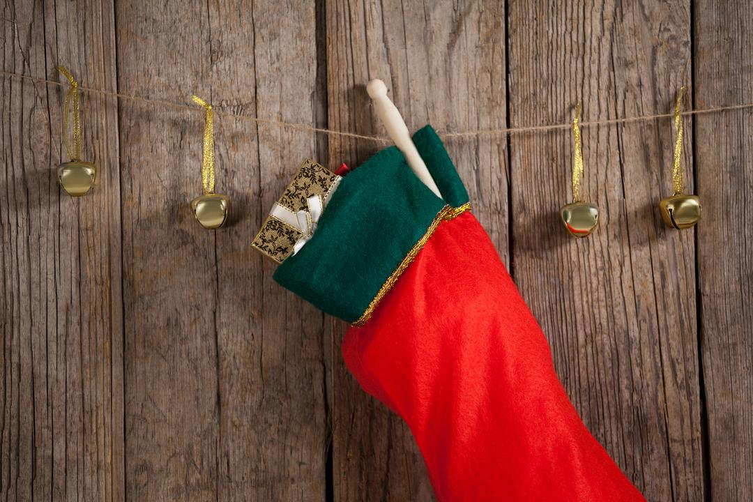 Christmas stocking and bells hanging against wooden wall during christmas time