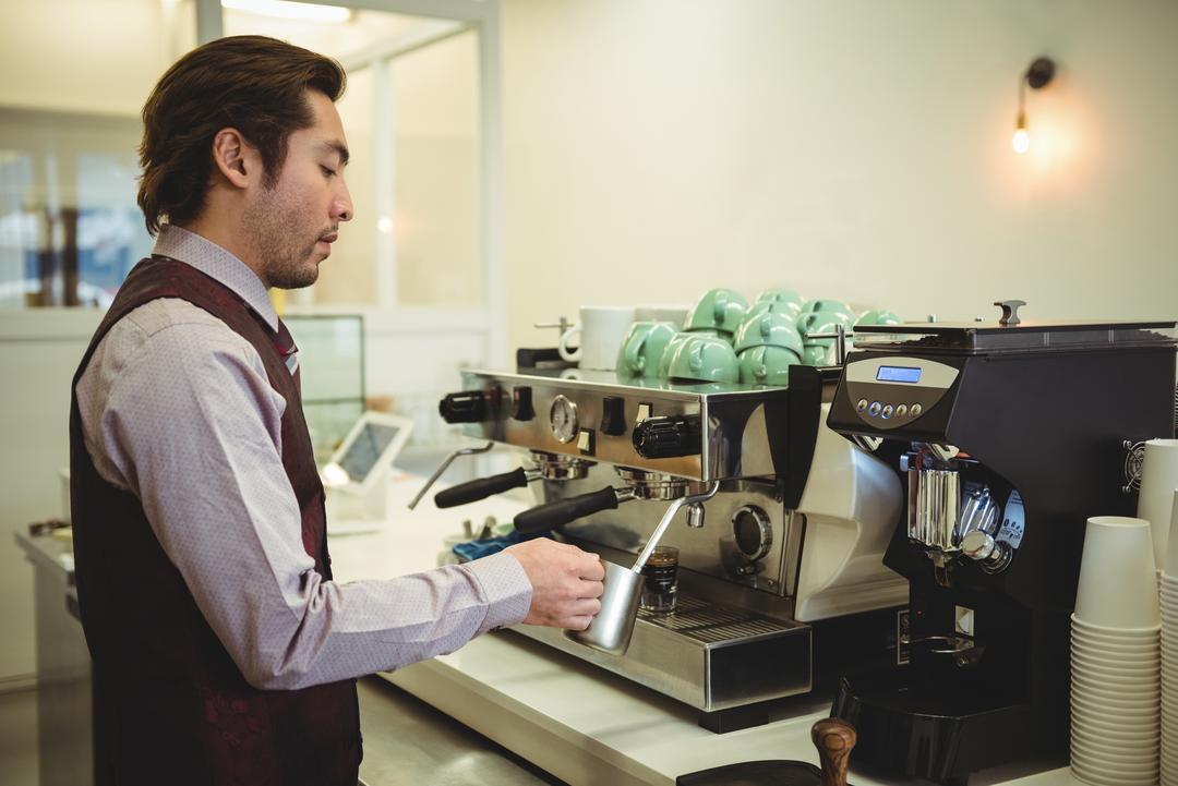 Man preparing coffee in coffee machine at coffee shop