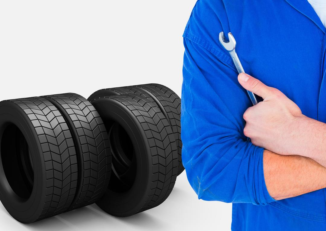 Digital composite image of mechanic holding wrench with tyres in background