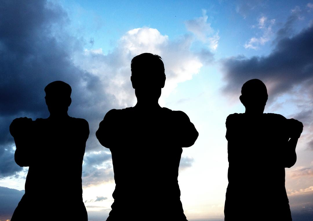 Silhouette of three determined people standing against blue cloudy sky