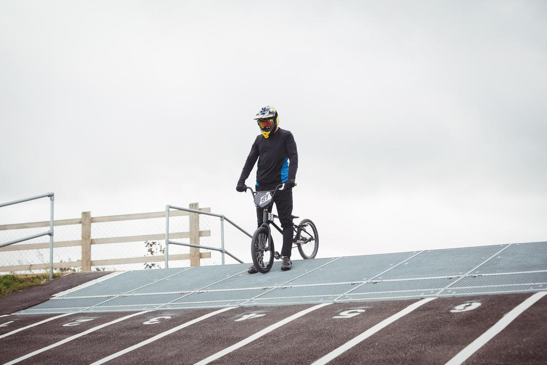 Cyclist standing with BMX bike at starting ramp in skatepark