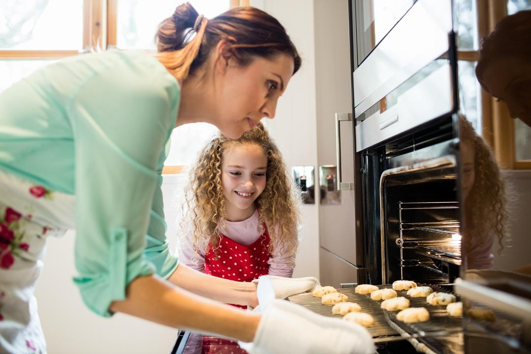 Mother and daughter preparing cookies in kitchen at home