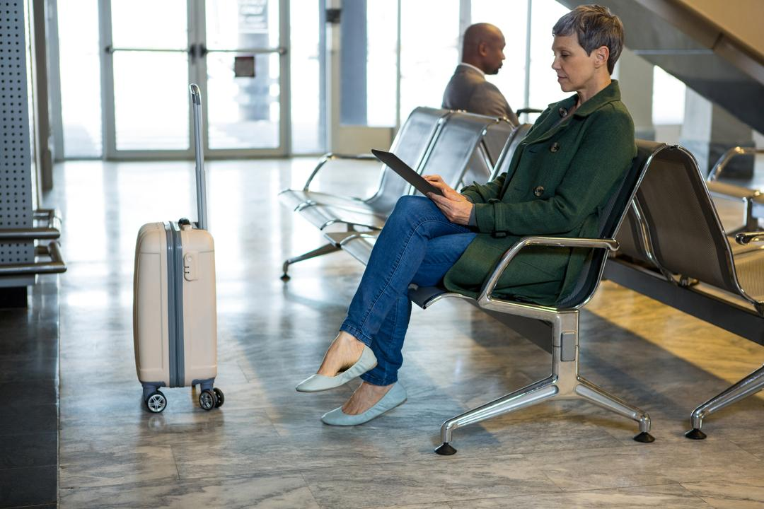 Woman using digital tablet while sitting at airport terminal