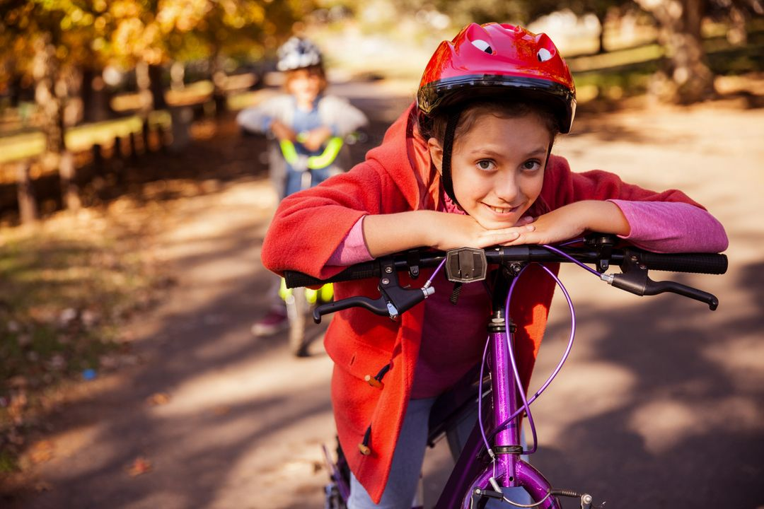 Portrait of smiling girl with mountain bike in park Free Stock Images from PikWizard