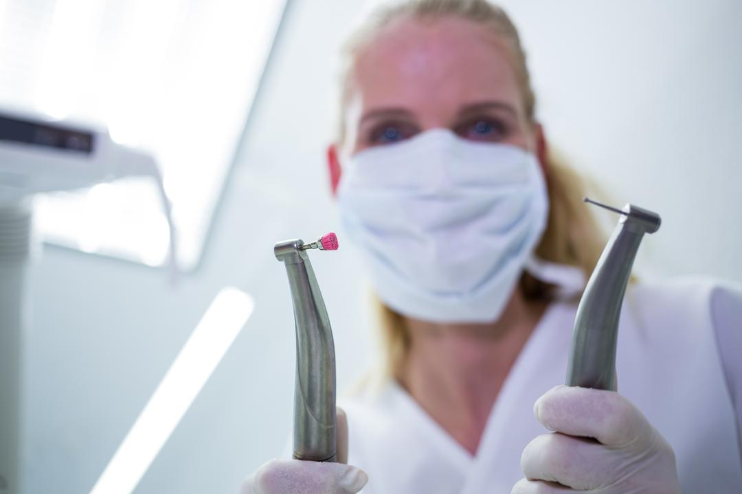 Female dentist with surgical mask holding dental instruments at clinic