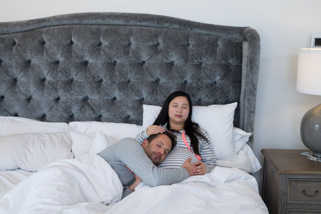 Man and pregnant woman relaxing peacefully in bedroom
