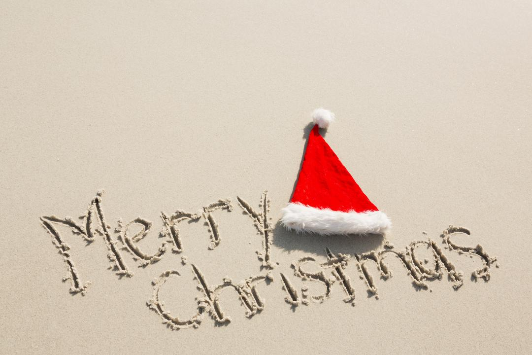 Merry Christmas written on sand with santa hat at beach