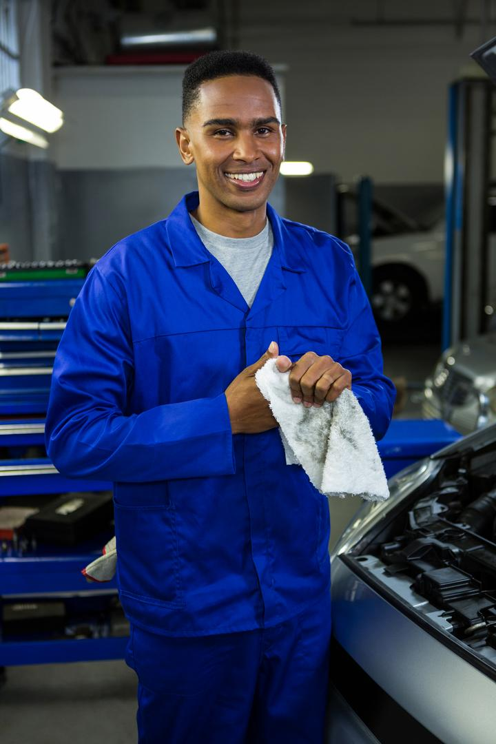 Portrait of happy mechanic wiping his hand in napkin at repair garage Free Stock Images from PikWizard
