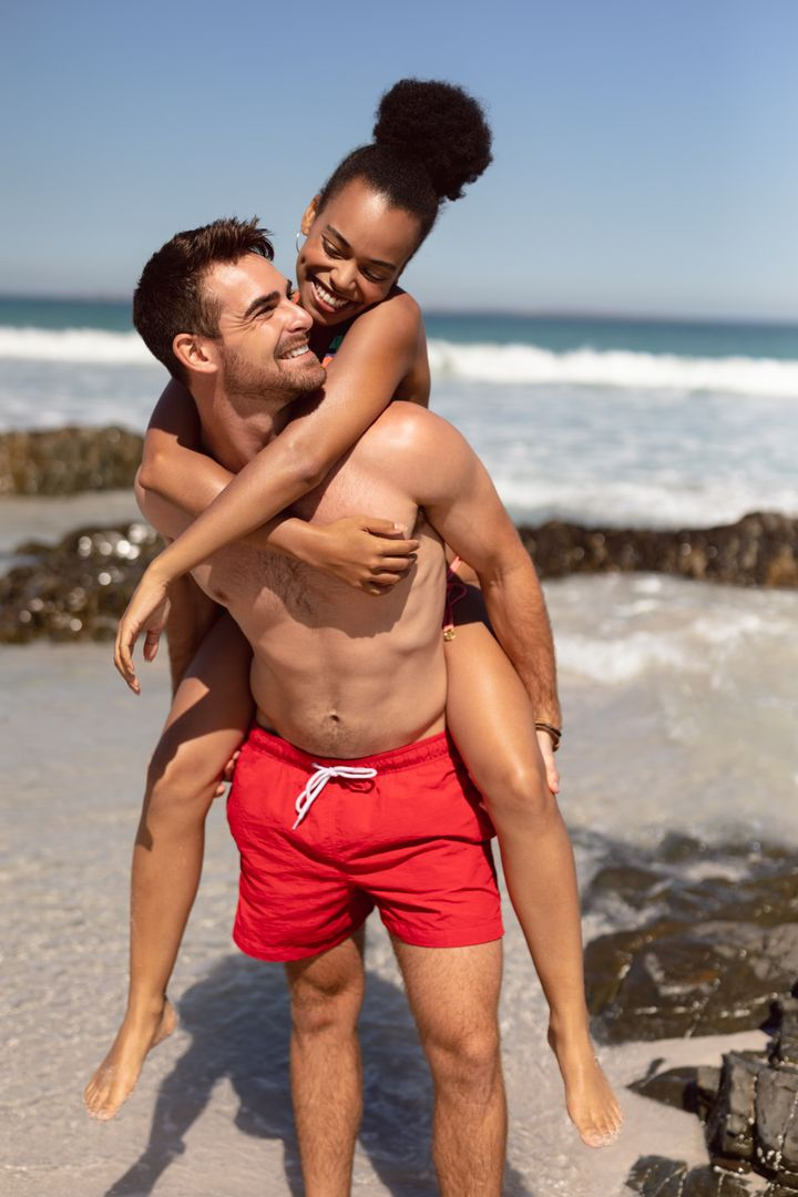 Front view of happy caucasian man giving piggyback to woman on beach in the sunshine Free Stock Images from PikWizard