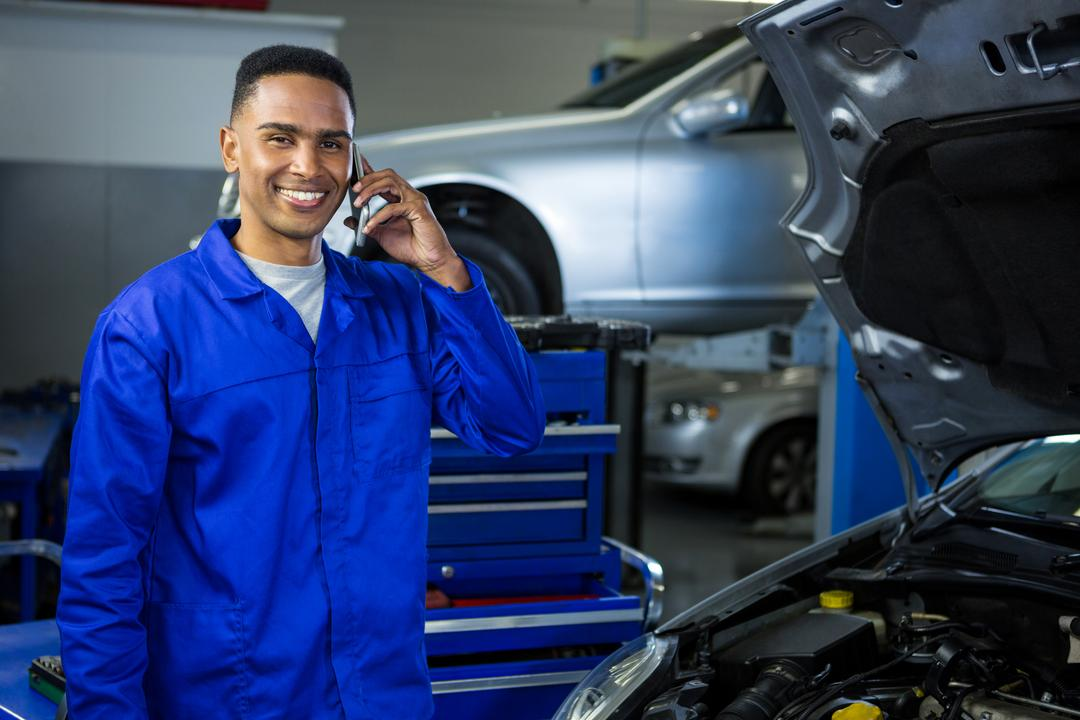 Portrait of smiling mechanic talking on a mobile phone at repair garage Free Stock Images from PikWizard