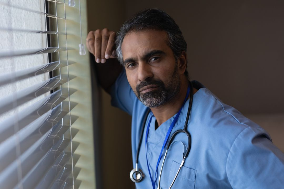 Portrait of mixed race male surgeon standing near window at hospital