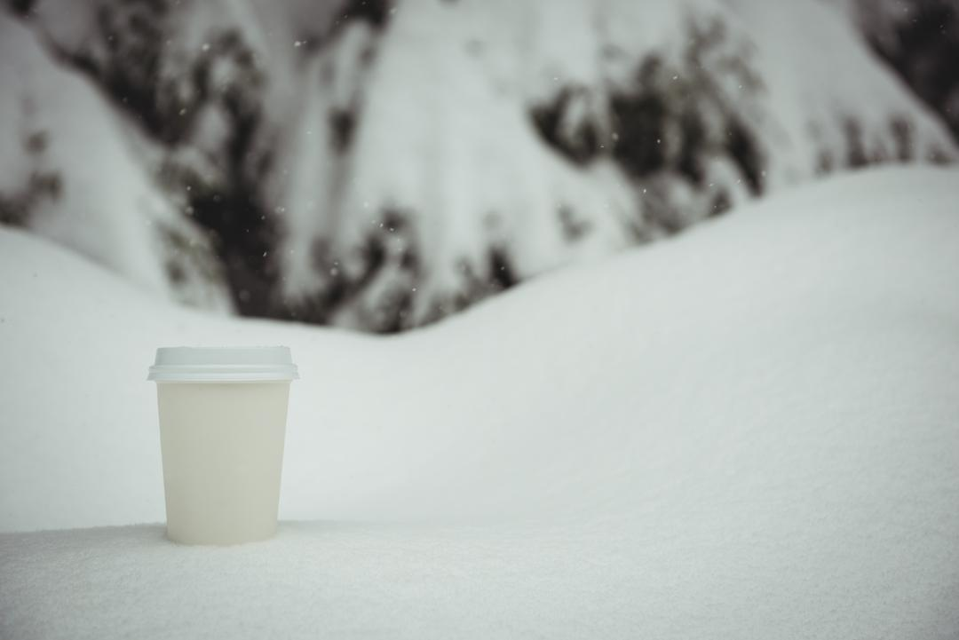 Disposable coffee cup in a snowy landscape during winter Free Stock Images from PikWizard
