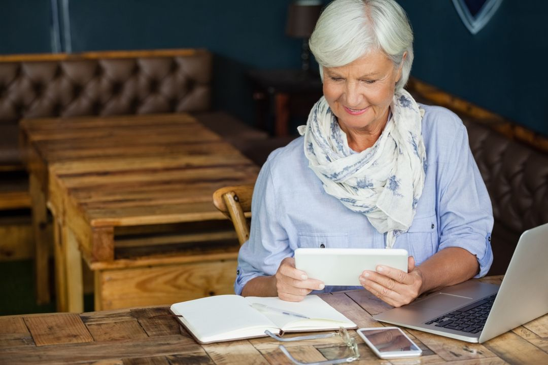 Smiling senior woman using digital tablet while sitting at table in cafe