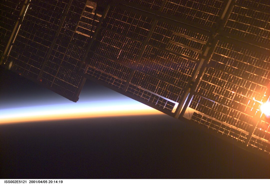 ISS002-E-5121 (5 April 2001) --- The solar panel supporting the Zvezda Service Module on the International Space Station (ISS)  is backdropped against Earth's horizon at dawn. The image was made by one of the Expedition Two crew members using a digital still camera.