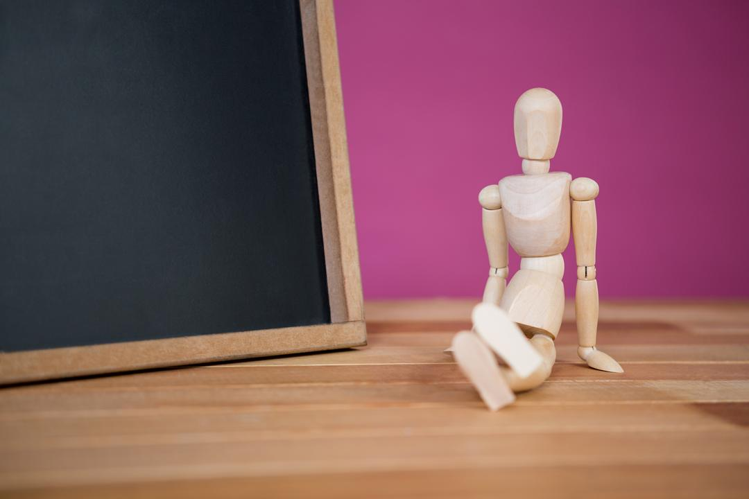 Conceptual image of figurine sitting near a chalkboard on a wooden floor