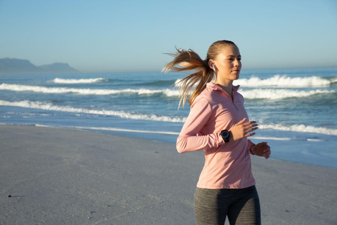 Caucasian woman wearing sports clothes, enjoying time at the beach on a sunny day, exercising and jogging. Healthy lifestyle leisure exercise. Free Stock Images from PikWizard