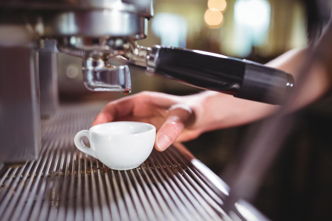 Waitress making cup of coffee at counter in kitchen at café