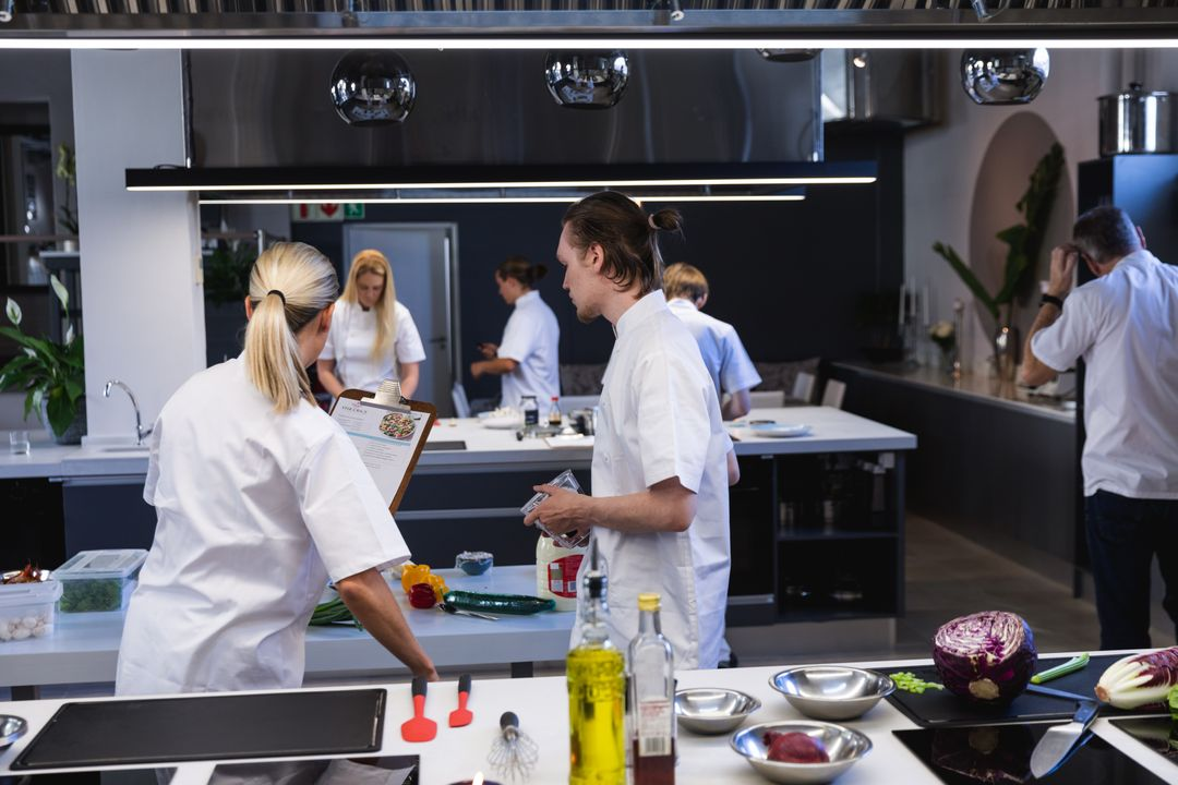 Group of chefs cooking in a modern busy kitchen, female chef holding a clipboard giving instructions. Cookery class at a restaurant kitchen. Workshop cooking food. Free Stock Images from PikWizard