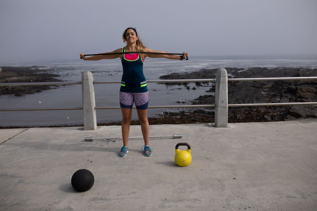 Front view of a strong Caucasian woman with long dark hair wearing sportswear exercising outdoors by the seaside on a sunny day, strength training stretching black rubber tape with her arms, ball and kettlebell next to her. Free Stock Images from PikWizard