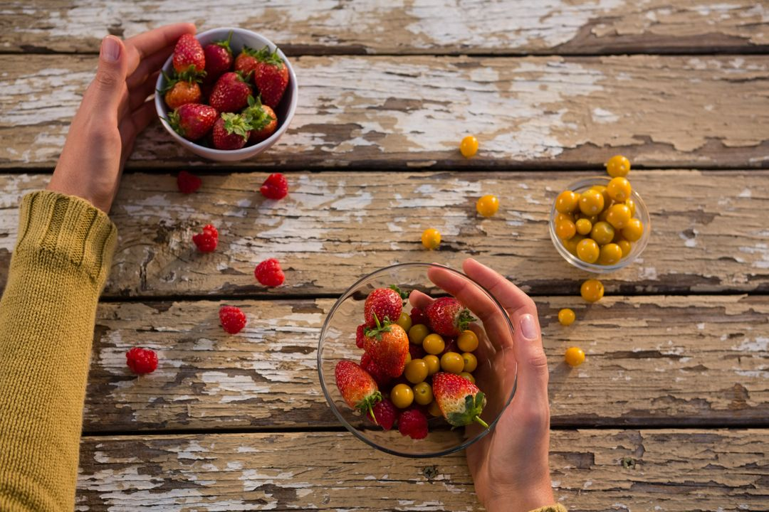 Cropped hand on woman holding berry fruits at wooden table Free Stock Images from PikWizard