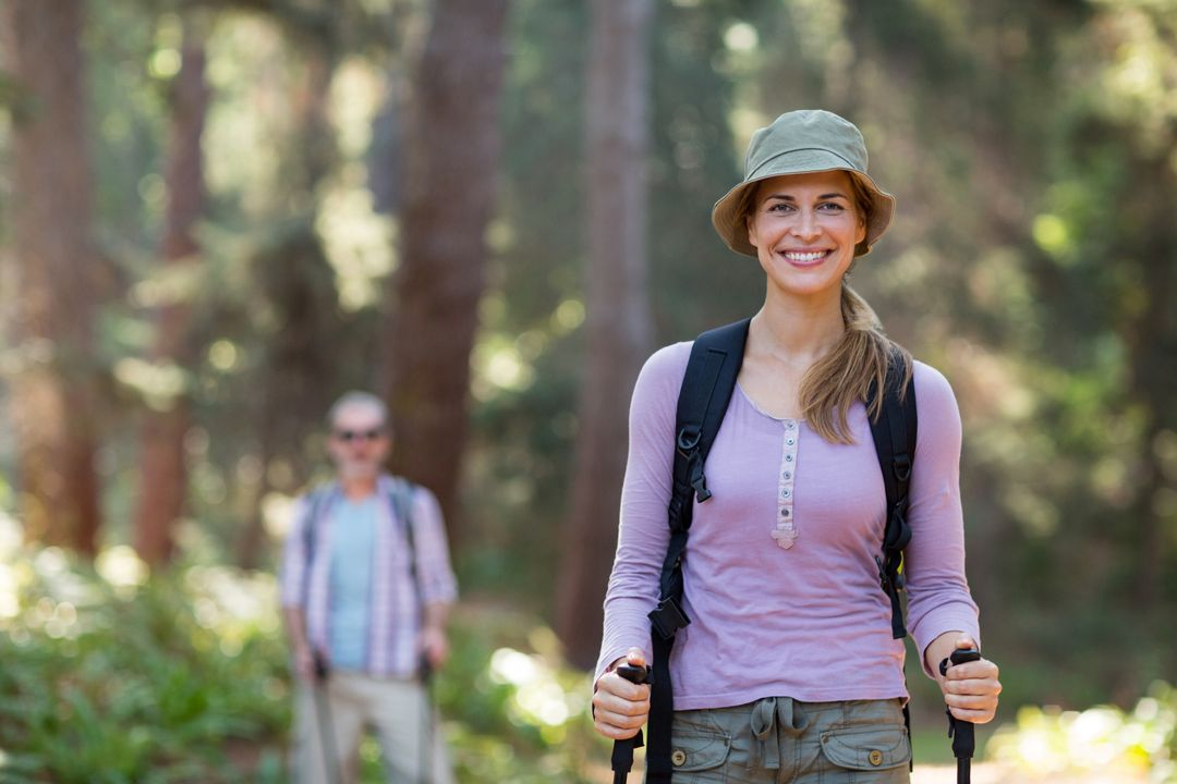 Smiling woman hiker hiking with trekking poles in forest Free Stock Images from PikWizard