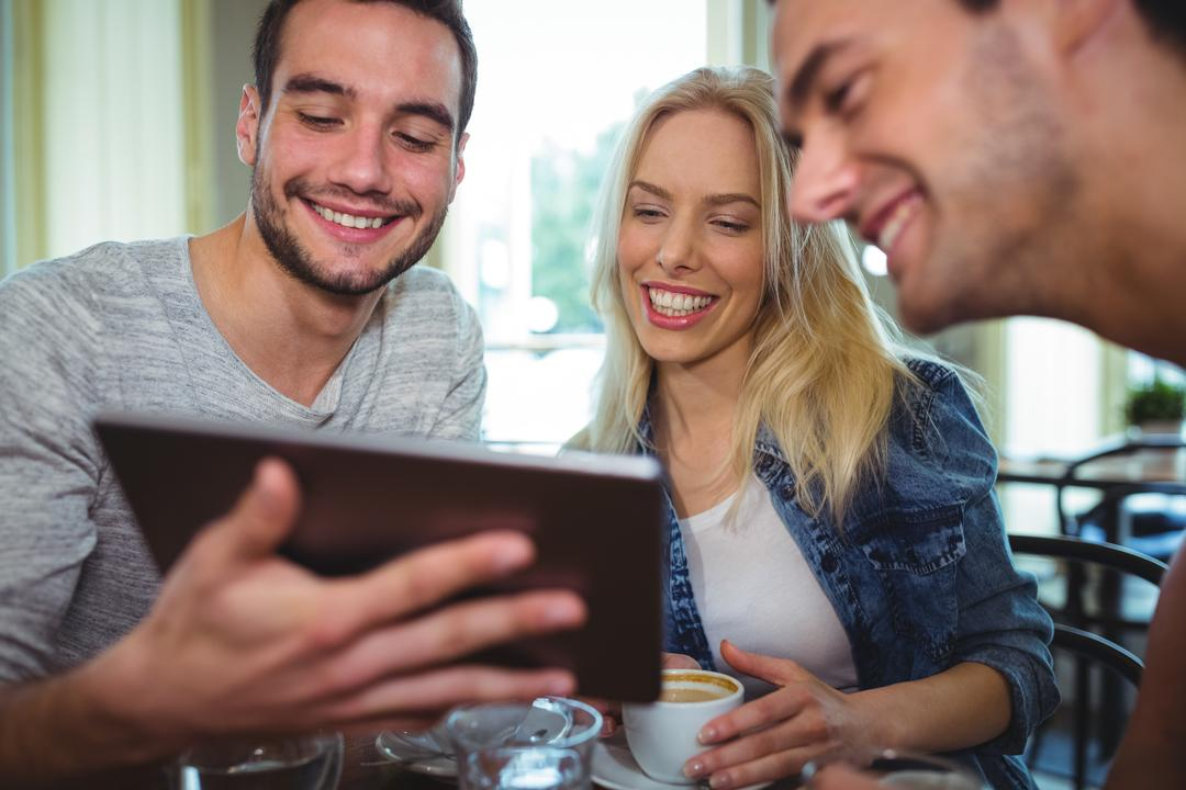 Smiling friends using digital tablet while having cup of coffee in café