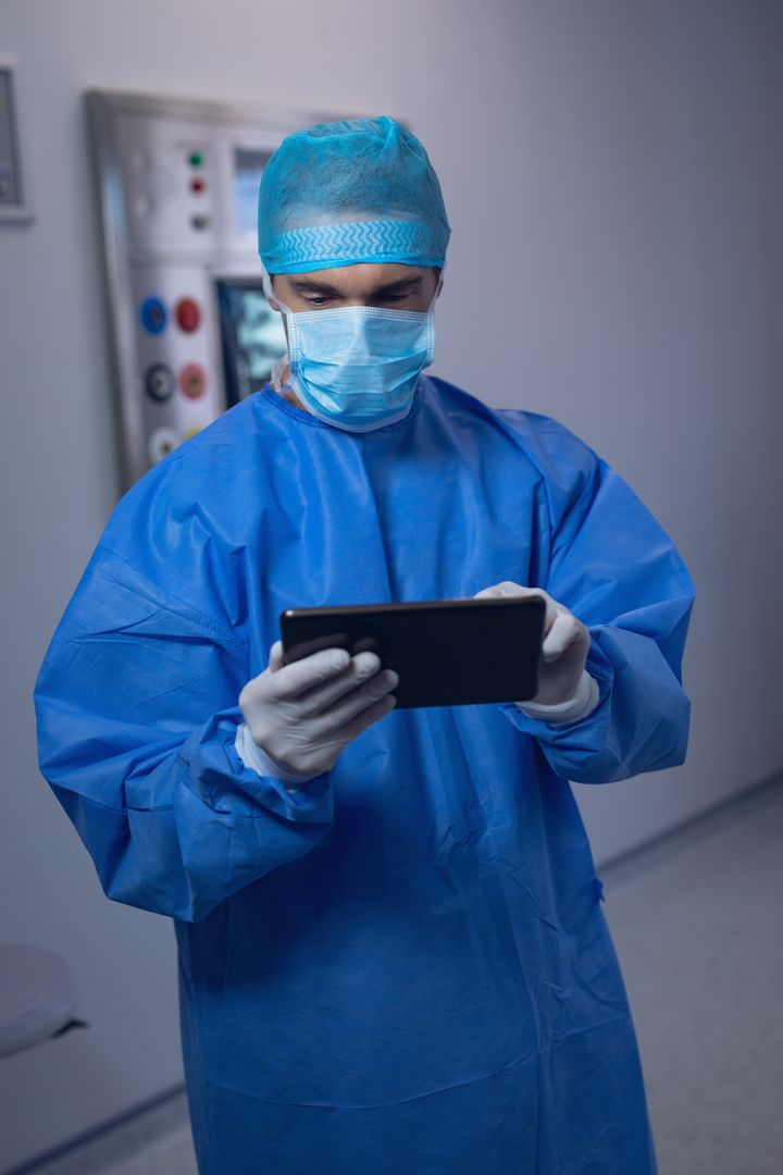 Male surgeon using digital tablet in operating room at hospital
