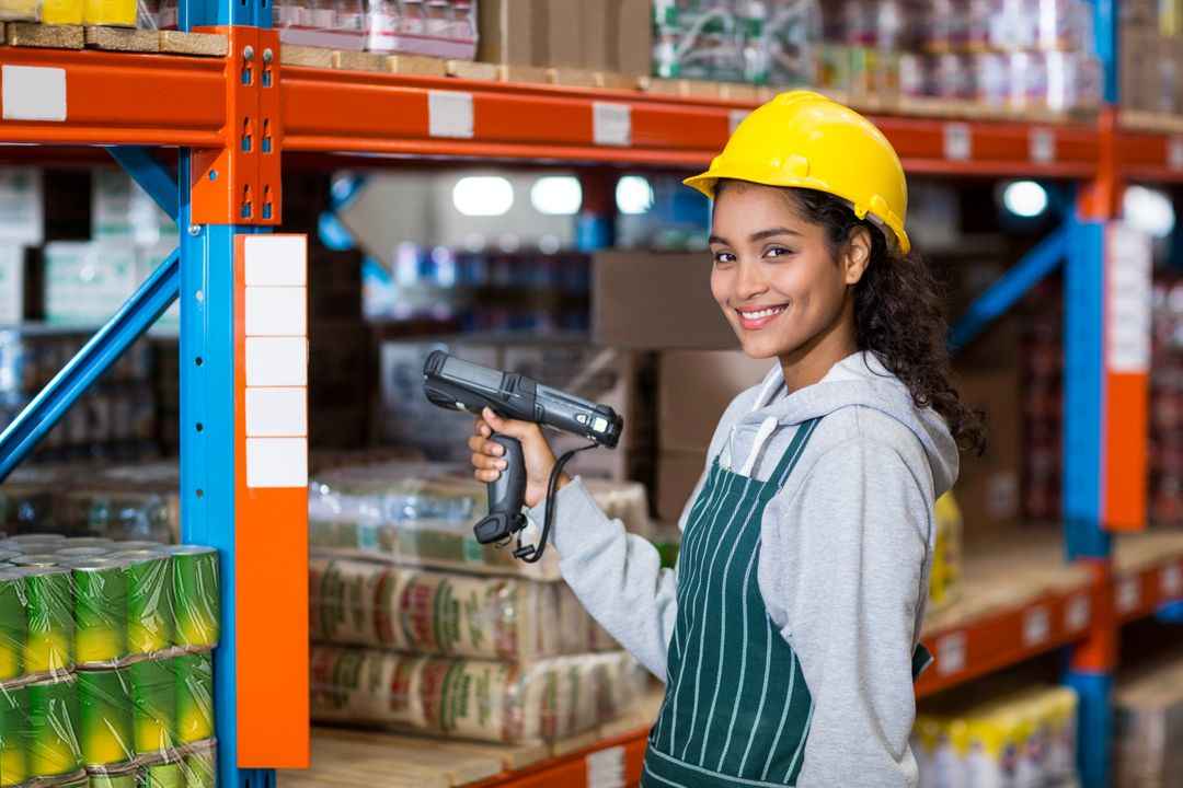 Portrait of female warehouse worker standing with barcode scanner in warehouse Free Stock Images from PikWizard