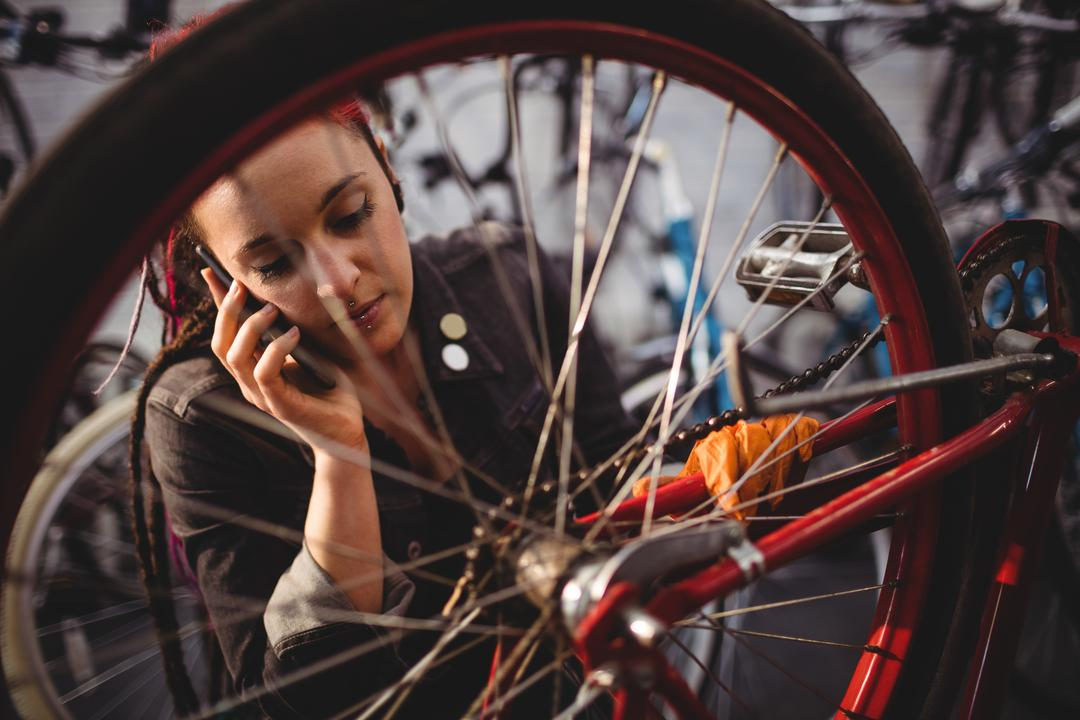 Mechanic talking on mobile phone while repairing bicycle in workshop Free Stock Images from PikWizard