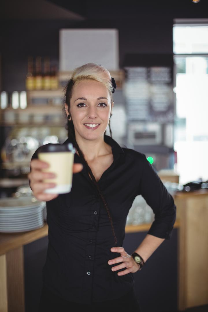 Portrait of waitress standing with disposable coffee cup in café Free Stock Images from PikWizard