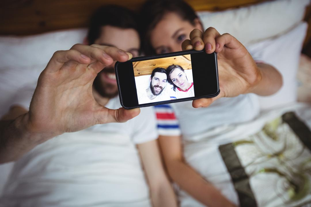 Couple clicking a photo from mobile phone on bed at bedroom