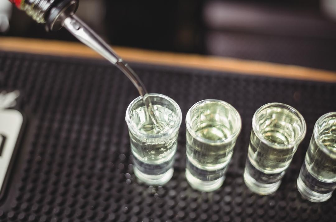 Close-up of bartender pouring tequila in shot glasses on bar counter at bar