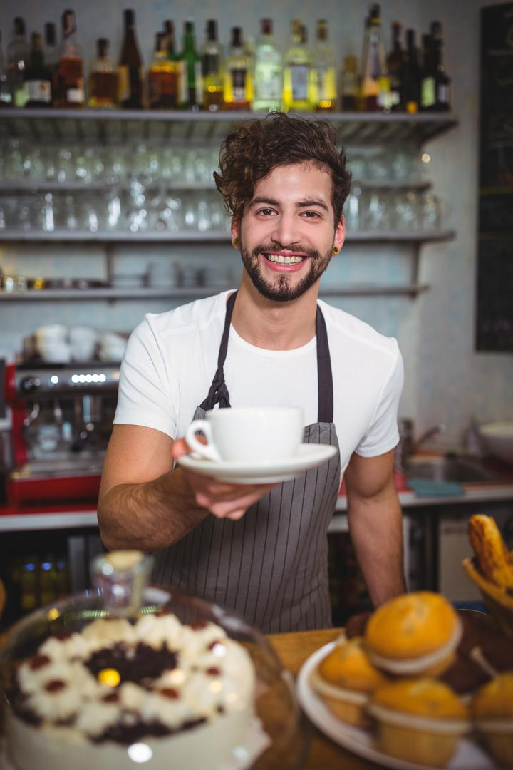 Portrait of smiling waiter serving a cup of coffee at counter in café