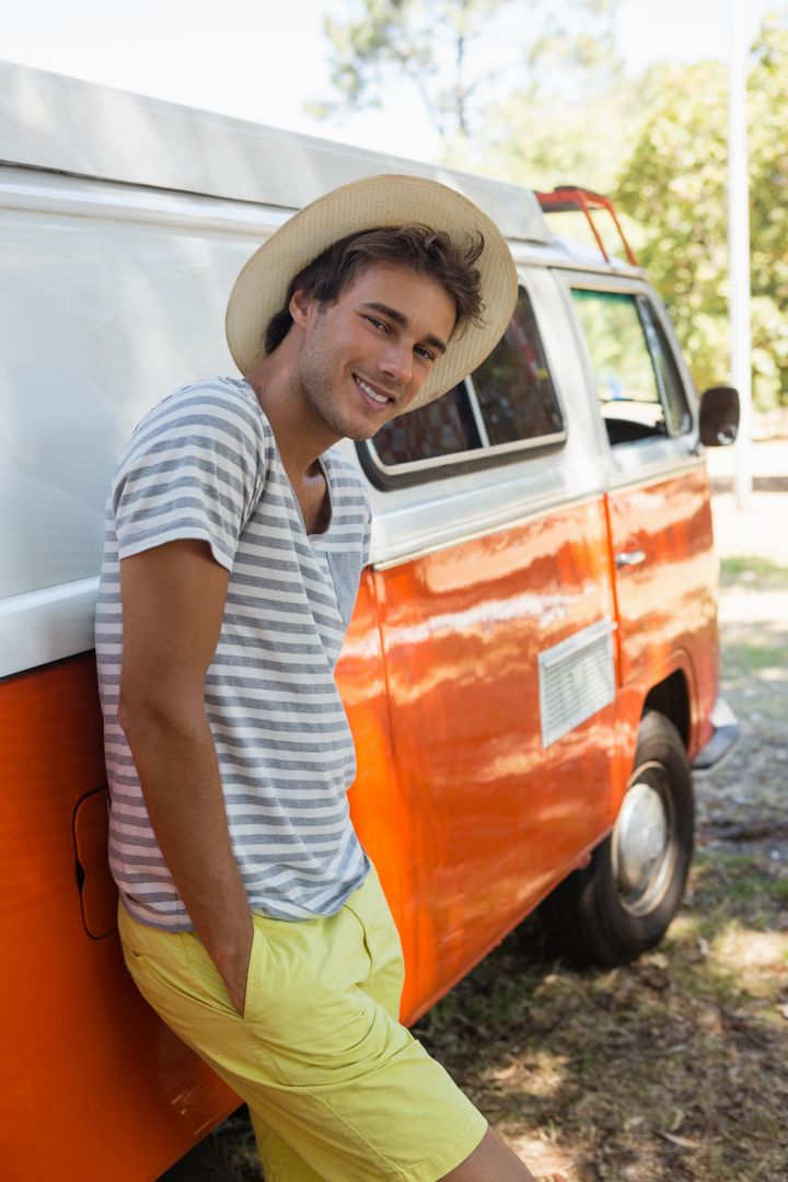 Portrait of man leaning on camper van in the park