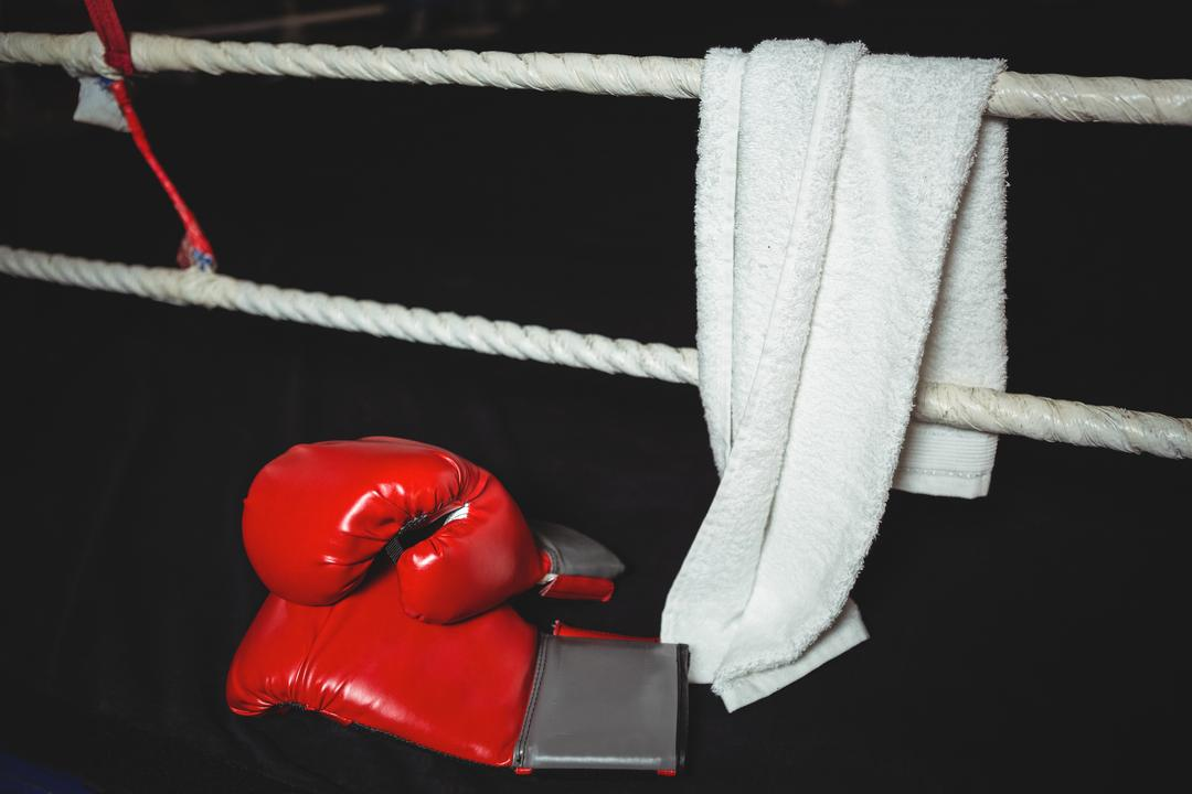 Boxing gloves and a towel in a corner of boxing ring